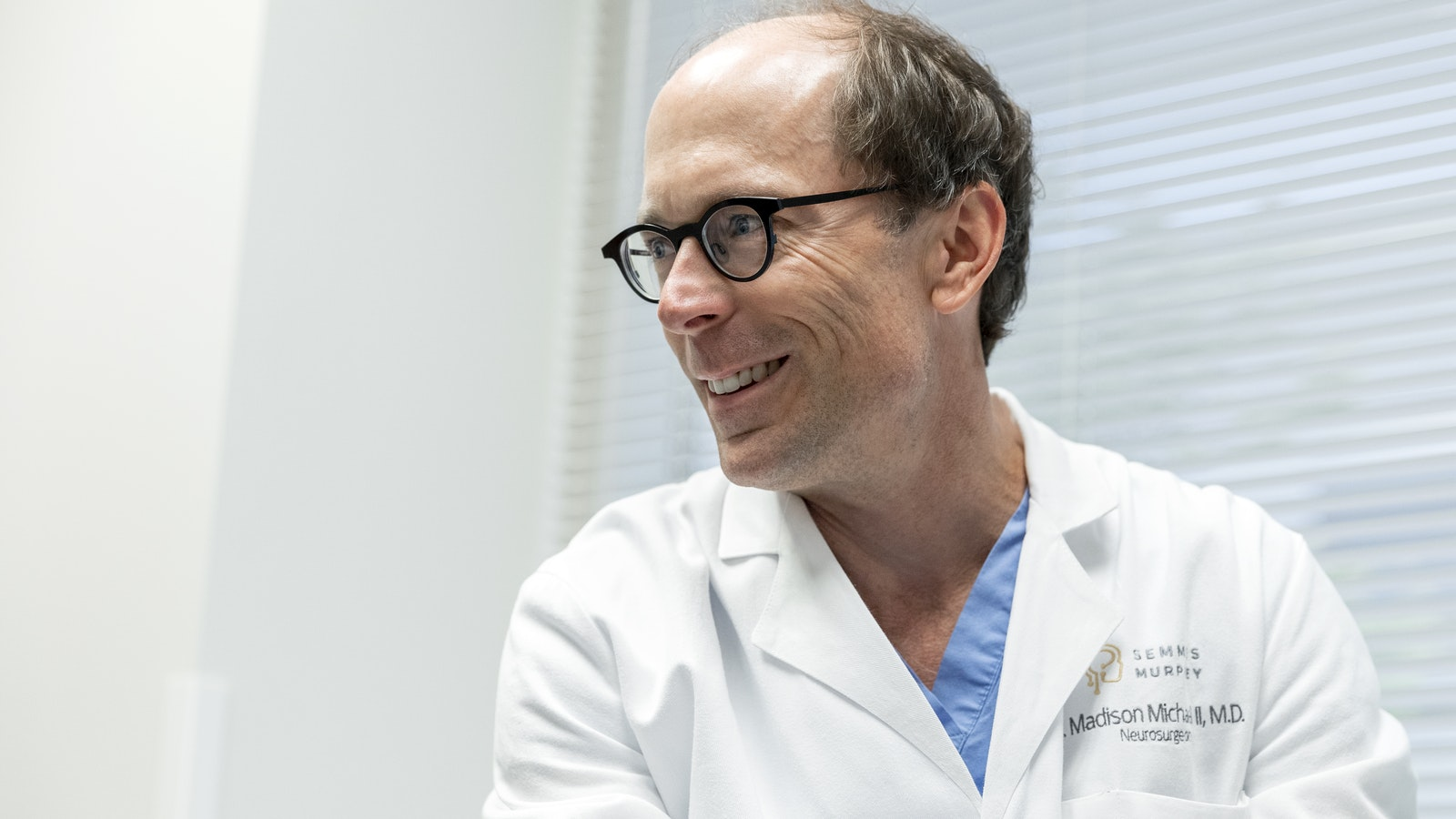 A doctor in a lab coat and glasses smiling and looking to the left