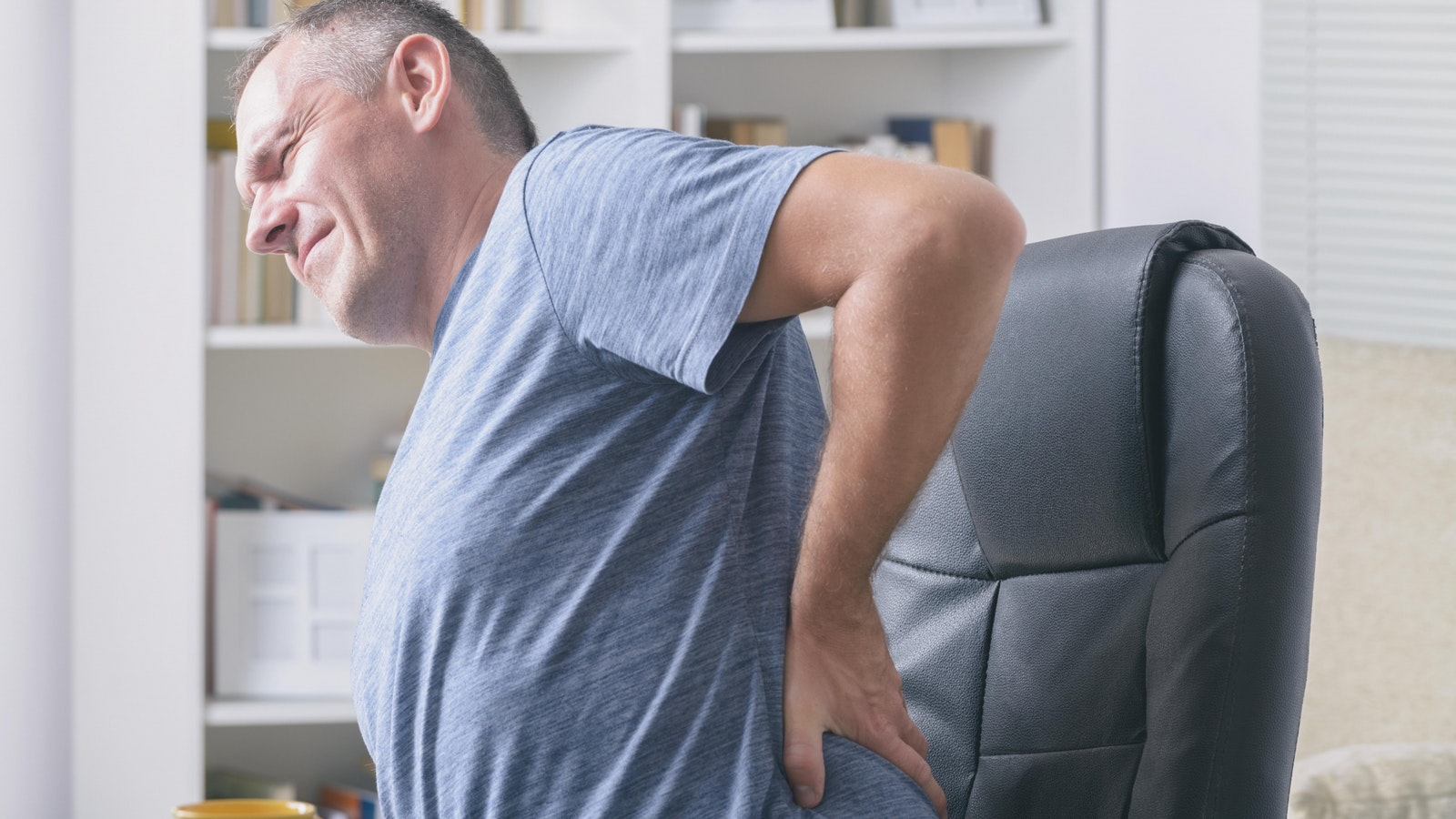 Man at desk with back pain wecompress com