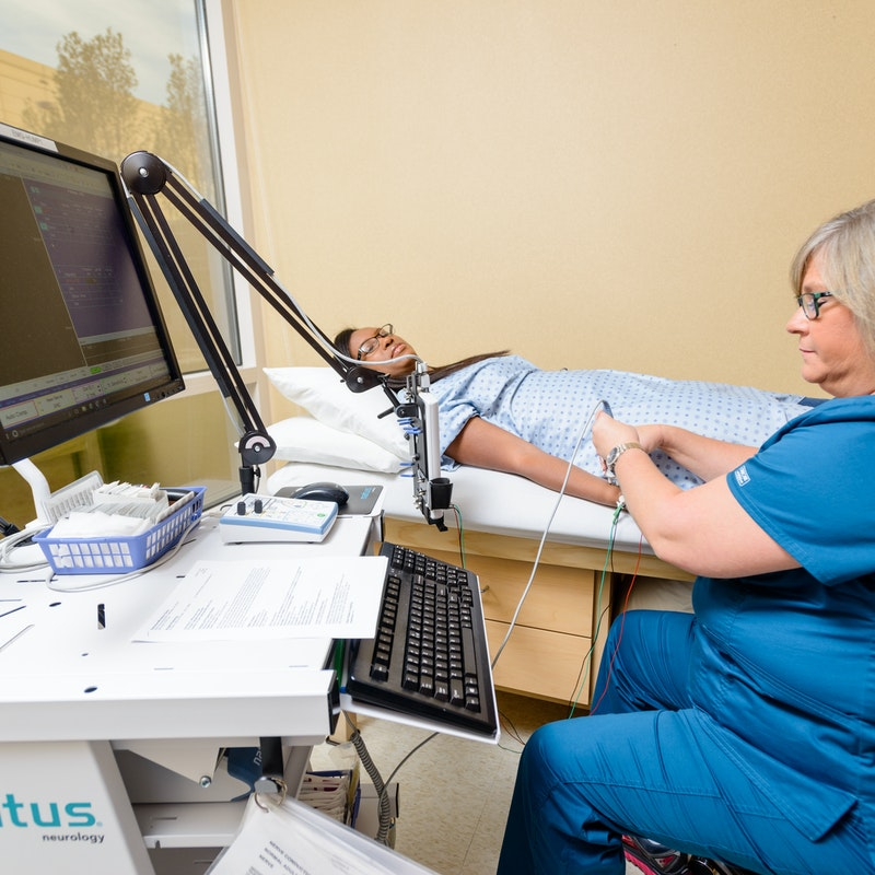 Nurse conducting an EMG on a patient's arm while the patient lays on their back