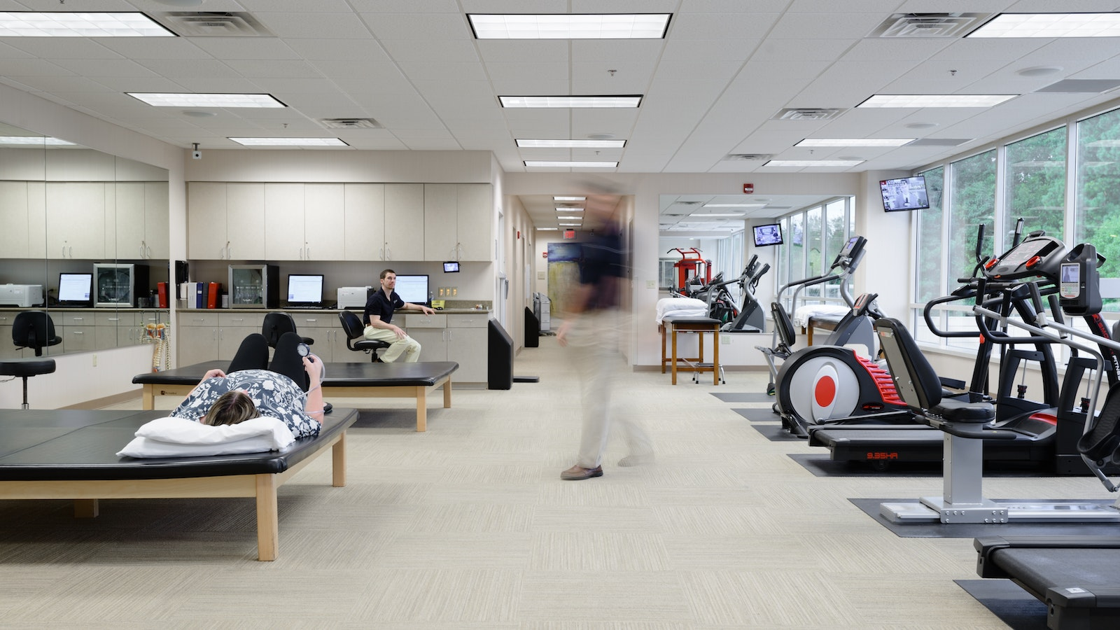 Blurred man walking through a physical therapy room